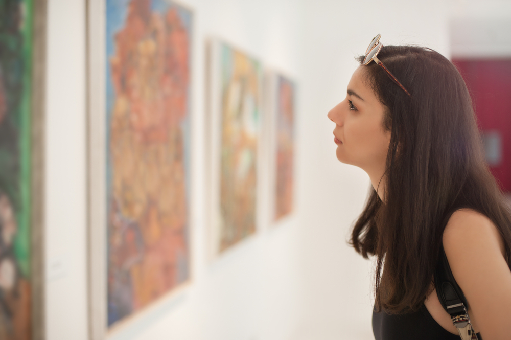a woman looking at art in a gallery