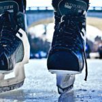 Black ice skating boots standing on an ice rink.