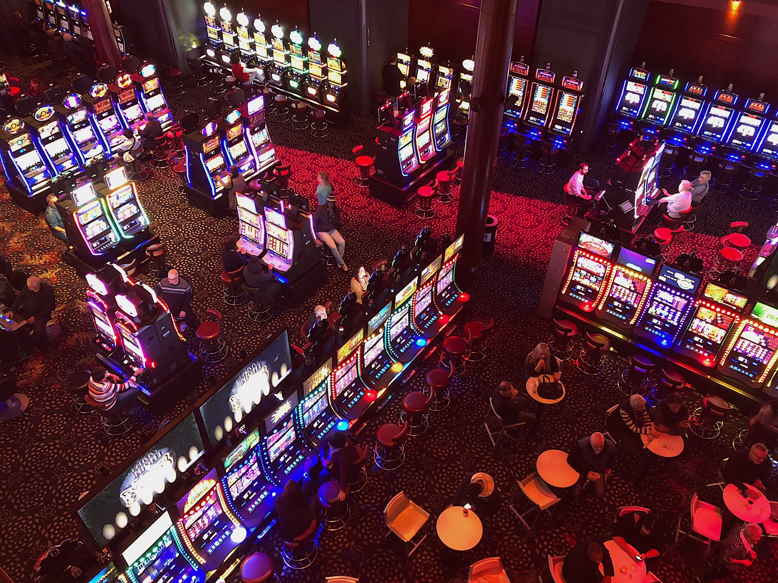 An aerial shot of a casino's slot machines and gambling tables.
