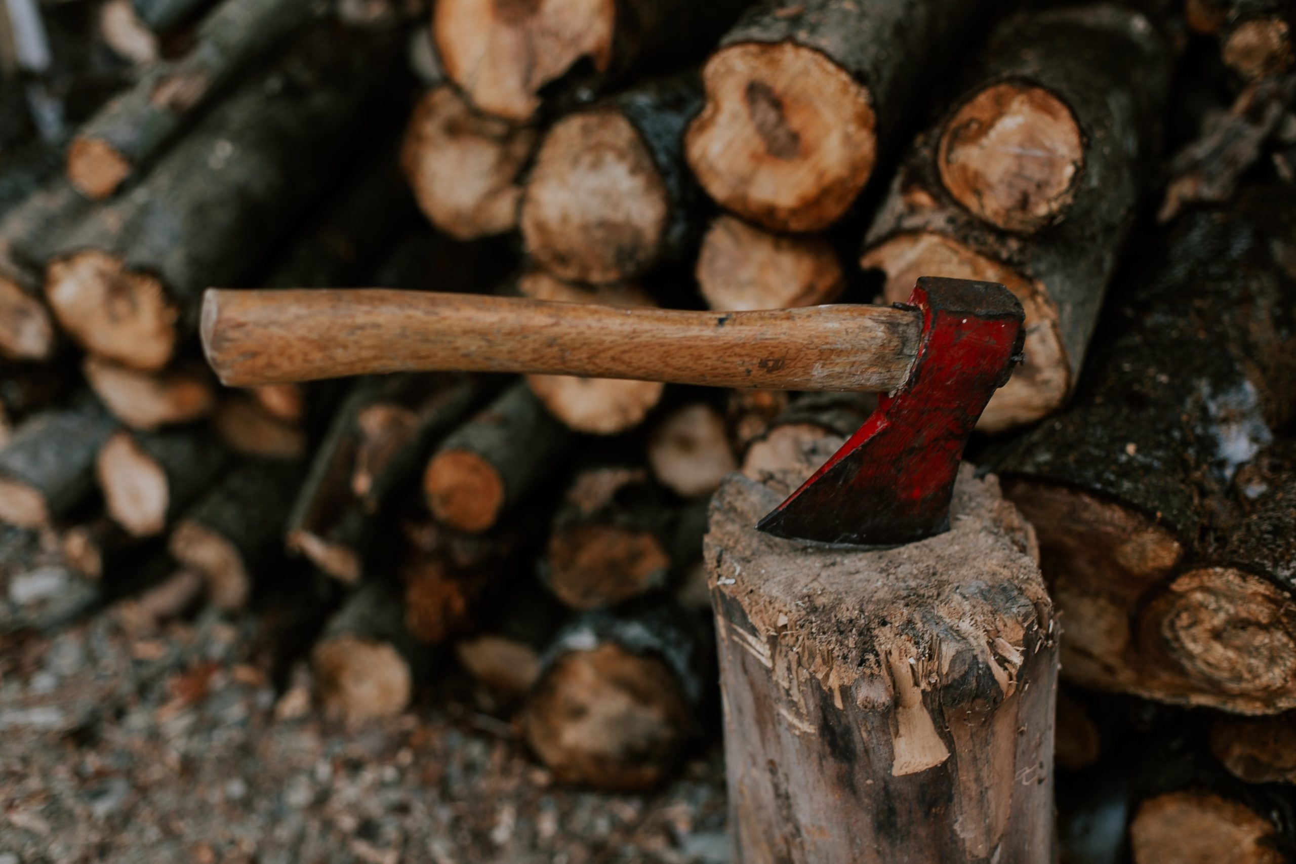 An ax stuck in a log in front of a pile of wood.