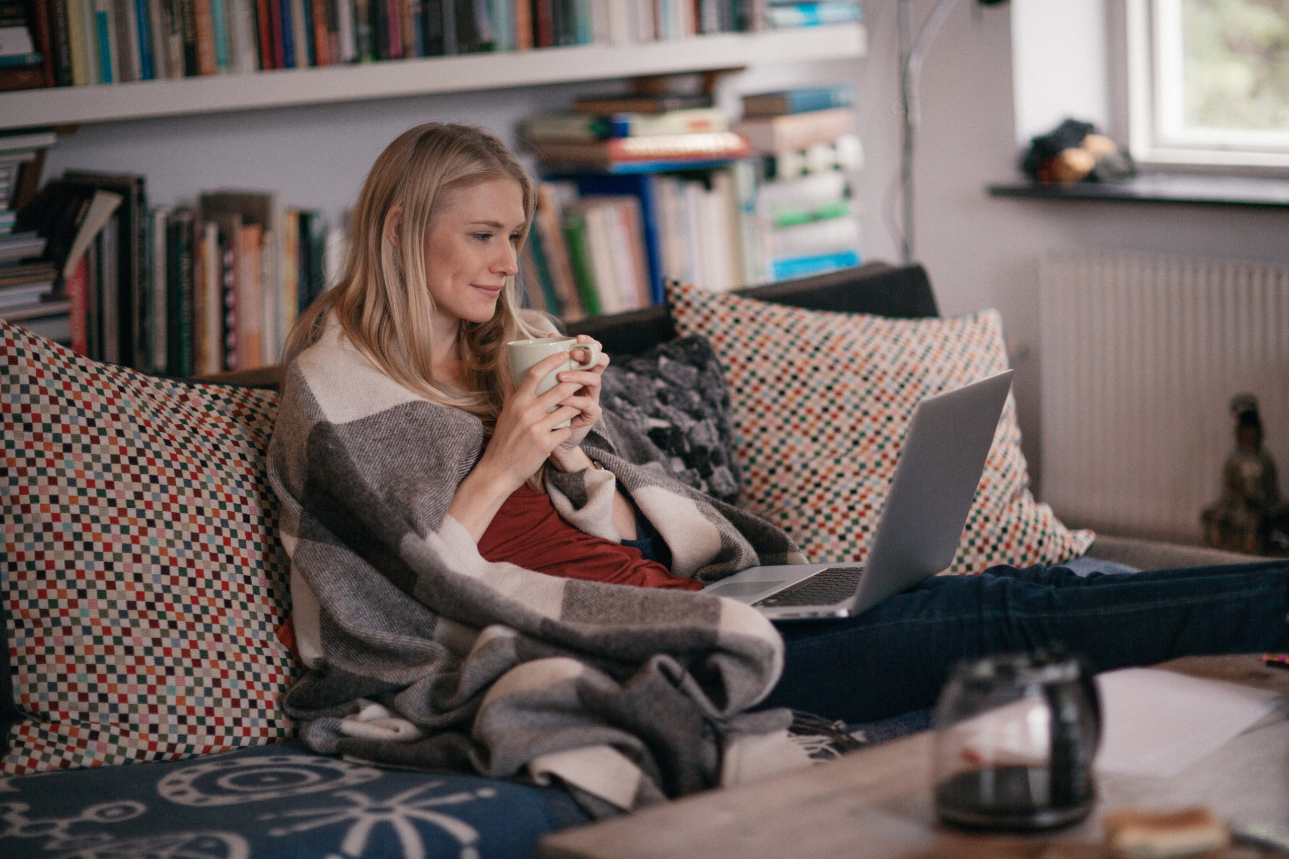 A woman watching a movie from her couch.
