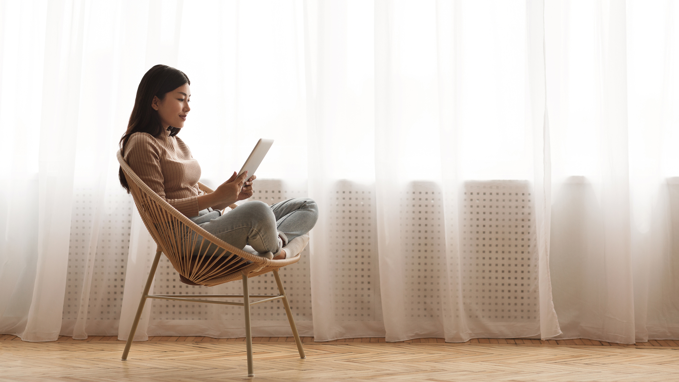 young woman reading an ebook in a wicker chair in minimalist apartment