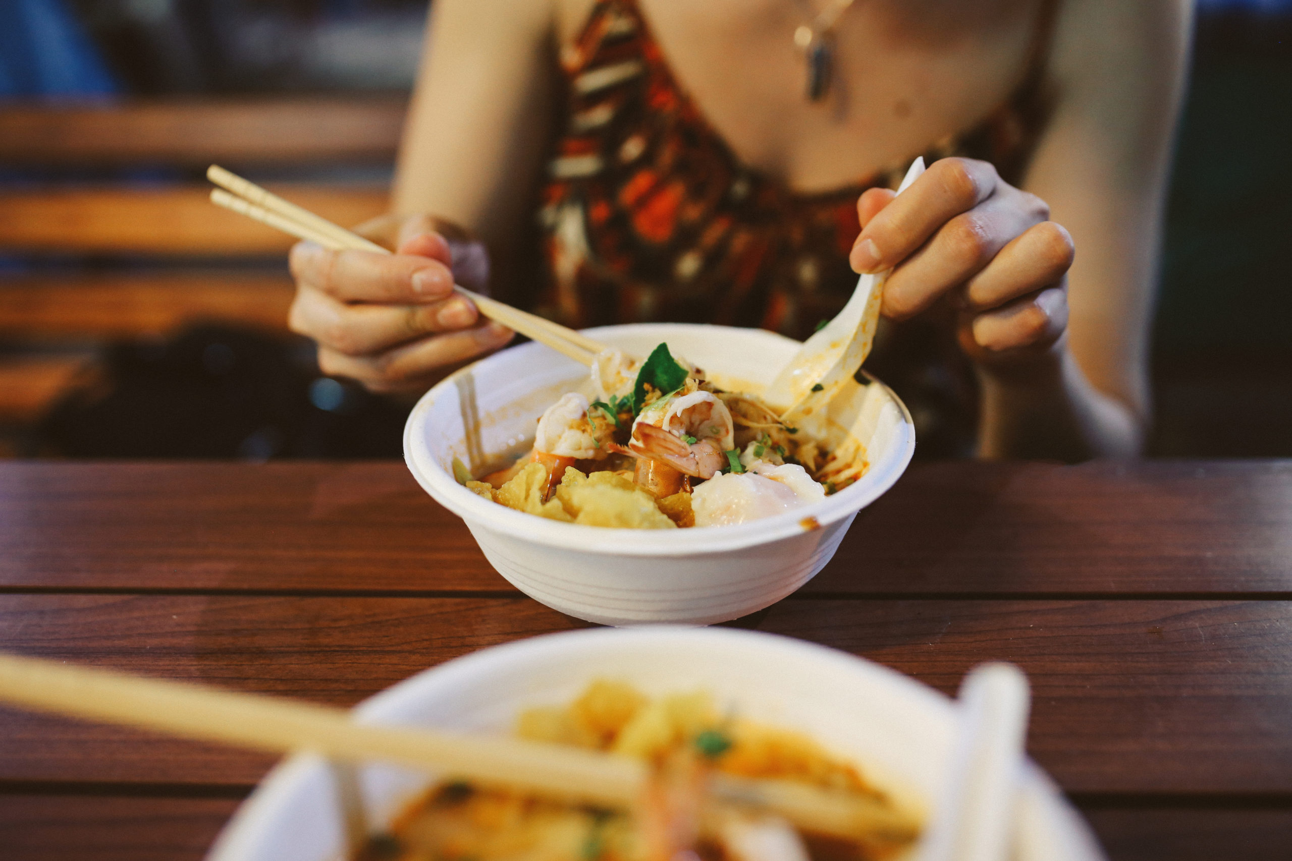 woman eating a bowl of takeout thai food with chopsticks and spoon