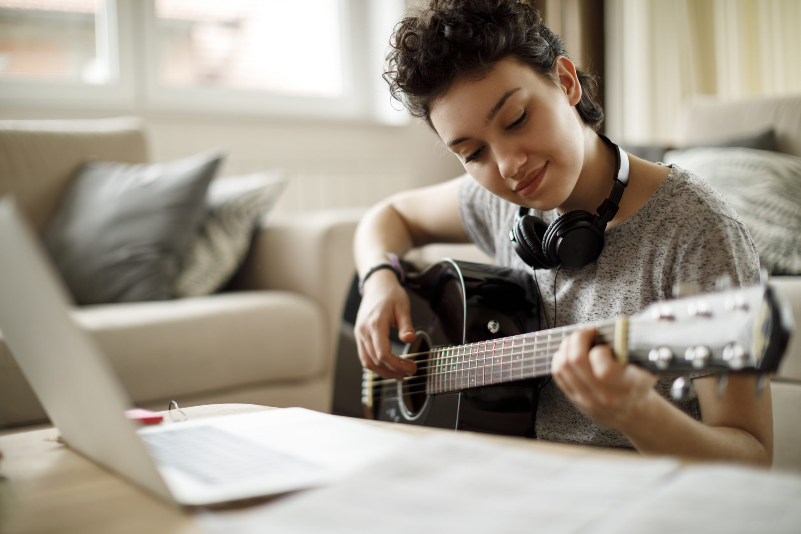 Smiling girl learning guitar from online music lessons