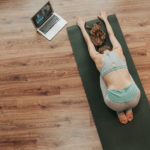 woman doing child's pose to a virtual yoga class at home