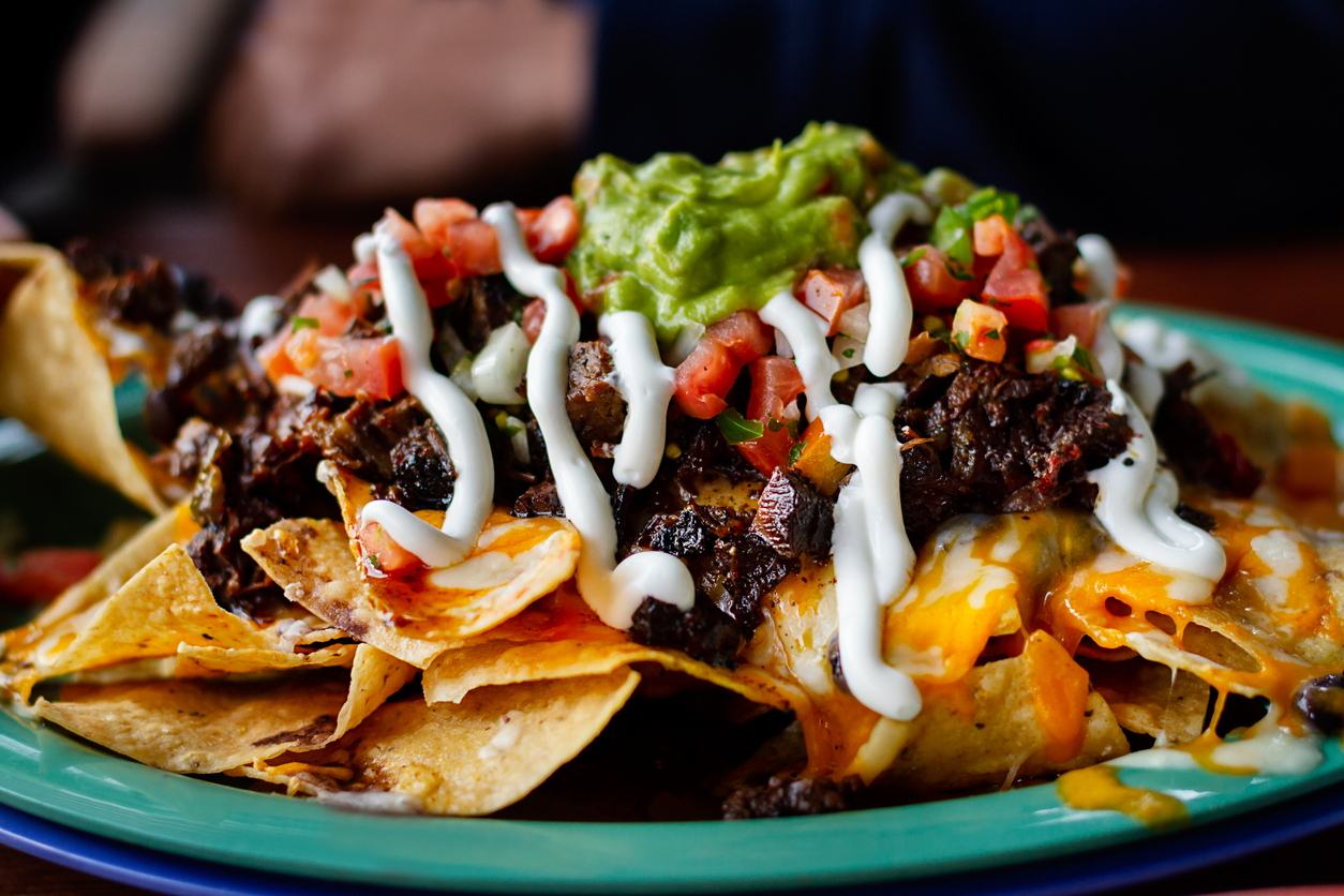 a plate of nachos with guacamole