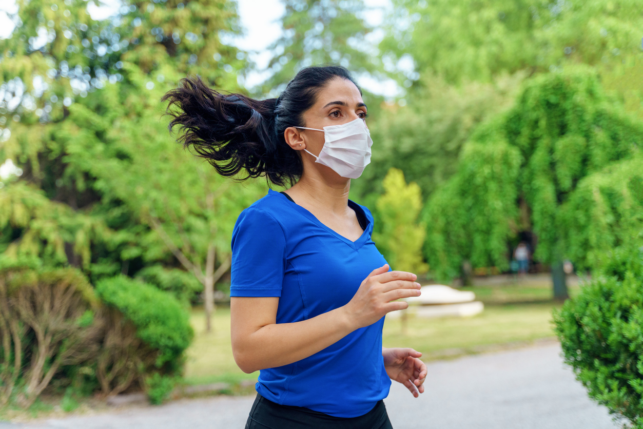 A woman wearing a face mask while running outside.