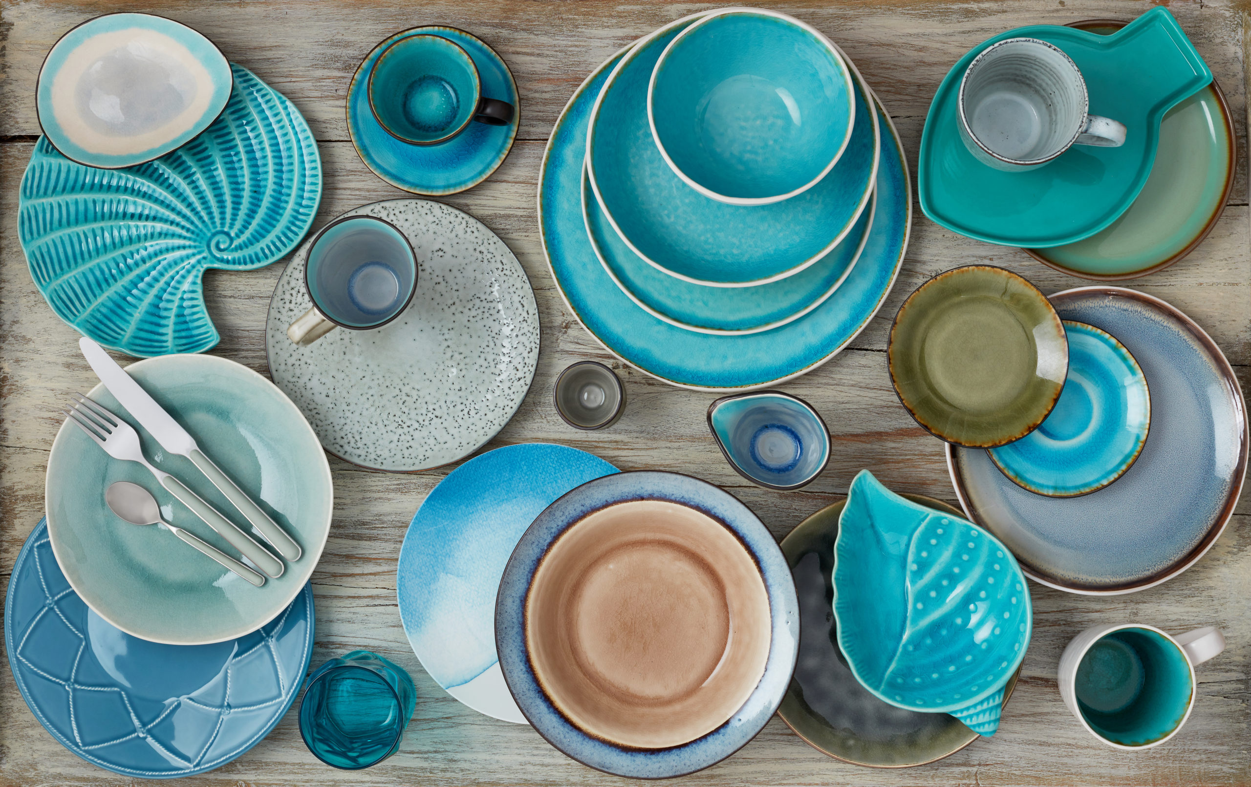 An assortment of teal pottery on a table.