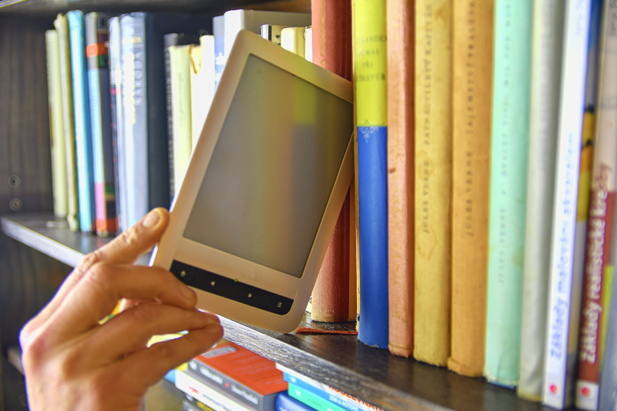 Someone grabbing a e-reader from a library shelf - Odenton Library online resources
