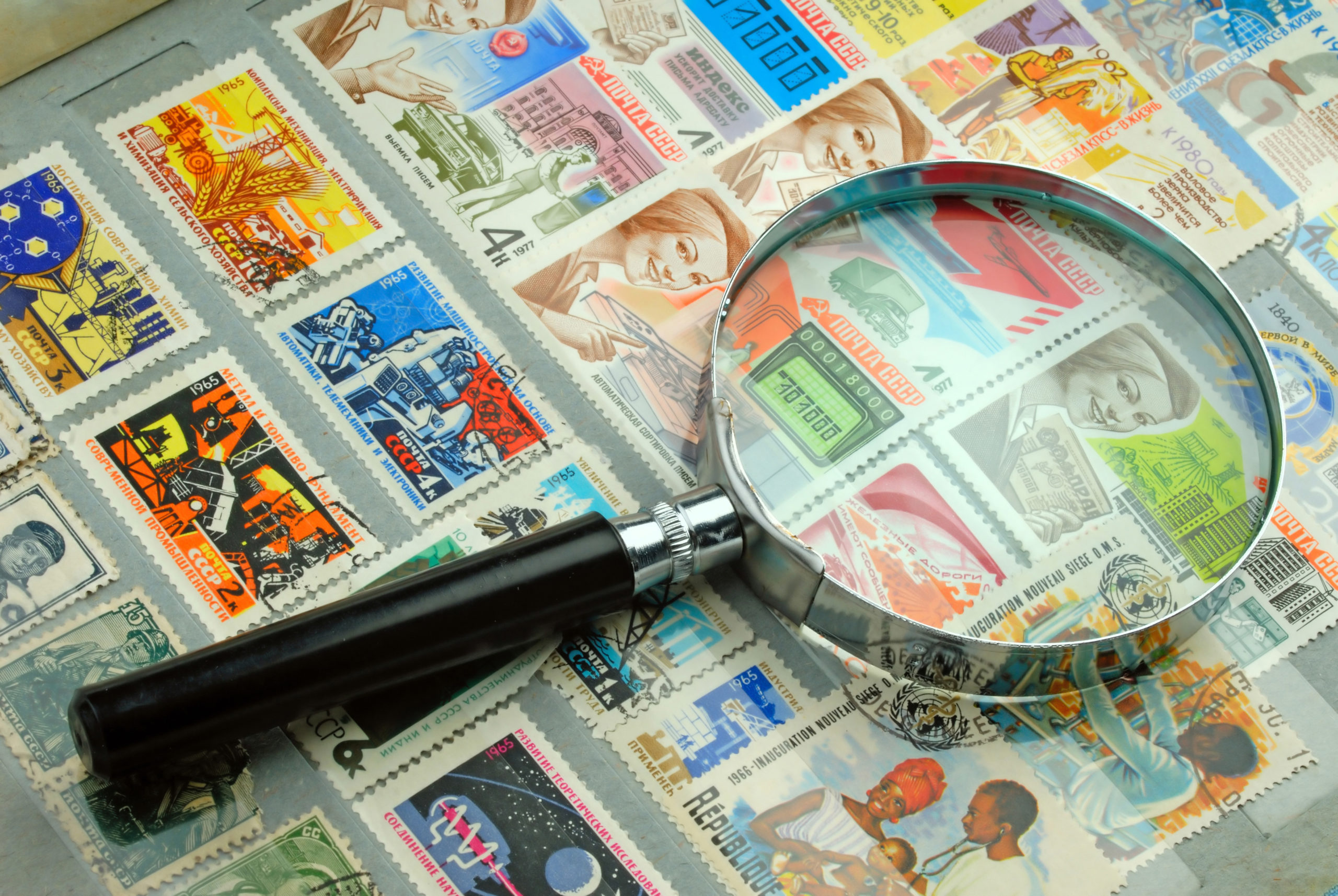 A magnifying glass laying on a stamp collection from the National Postal Museum