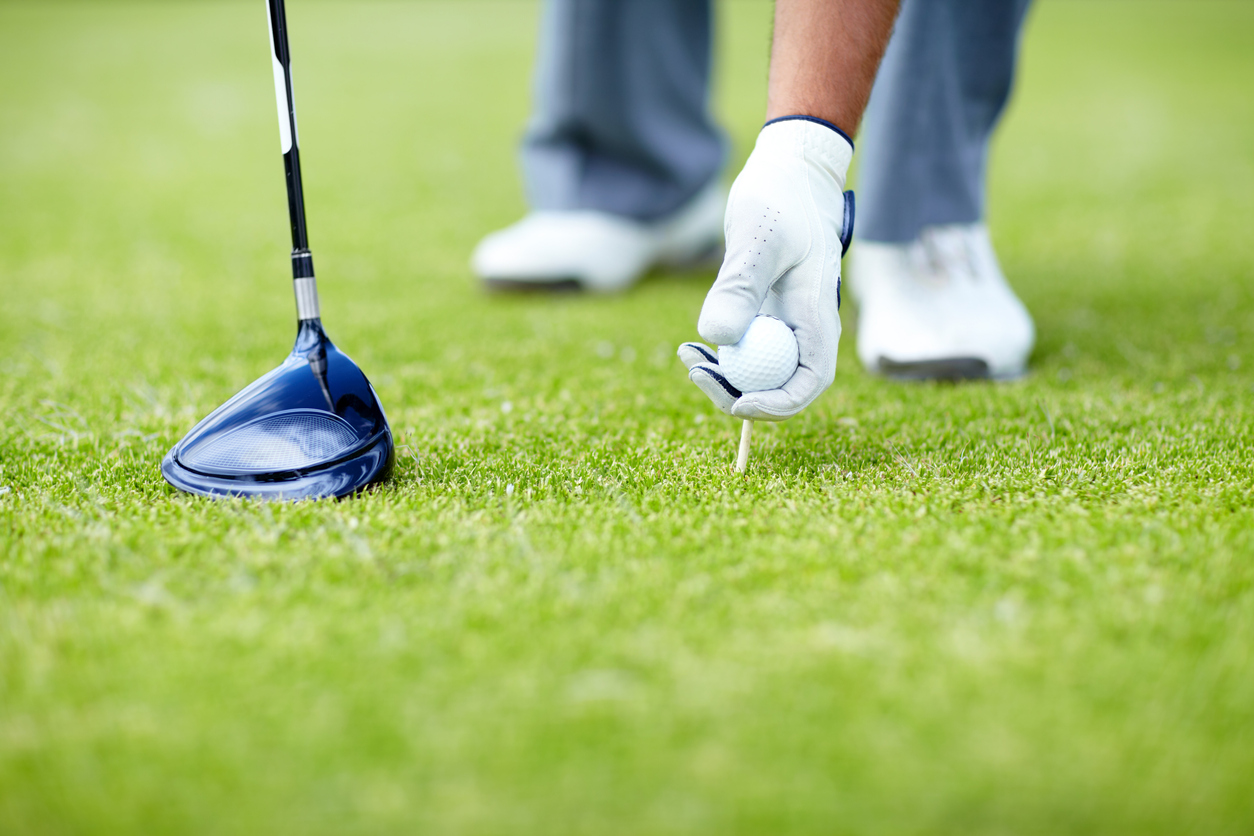 person placing golf ball on a tee | golf course near Jessup