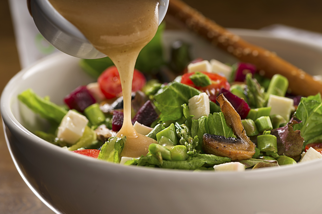 Someone pouring dressing over a salad from a Jessup restaurant