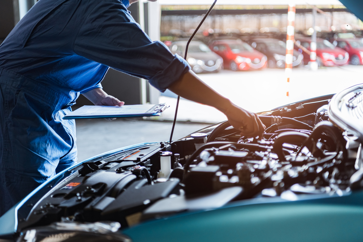 A mechanic reaching into the hood of a car | auto repair shops in Jessup