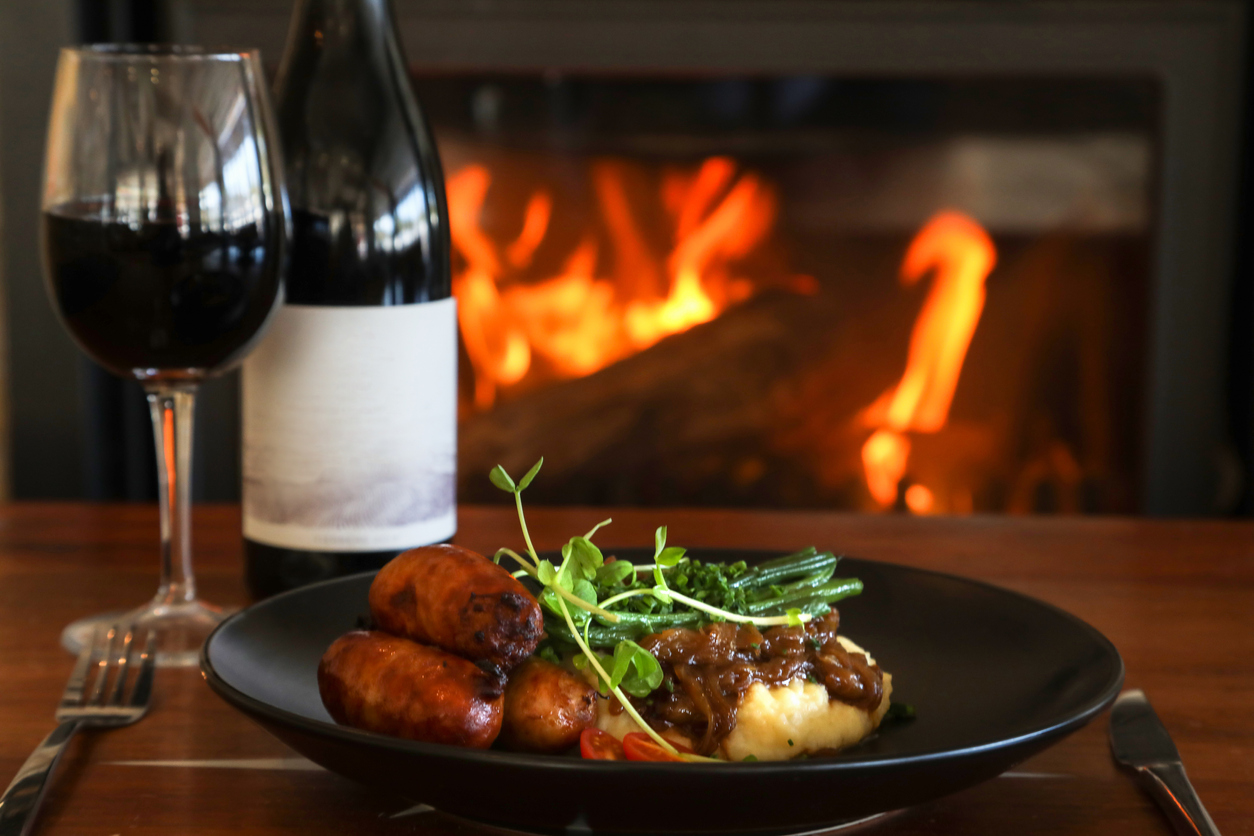 food and wine next to a fire | fireside meal in Jessup