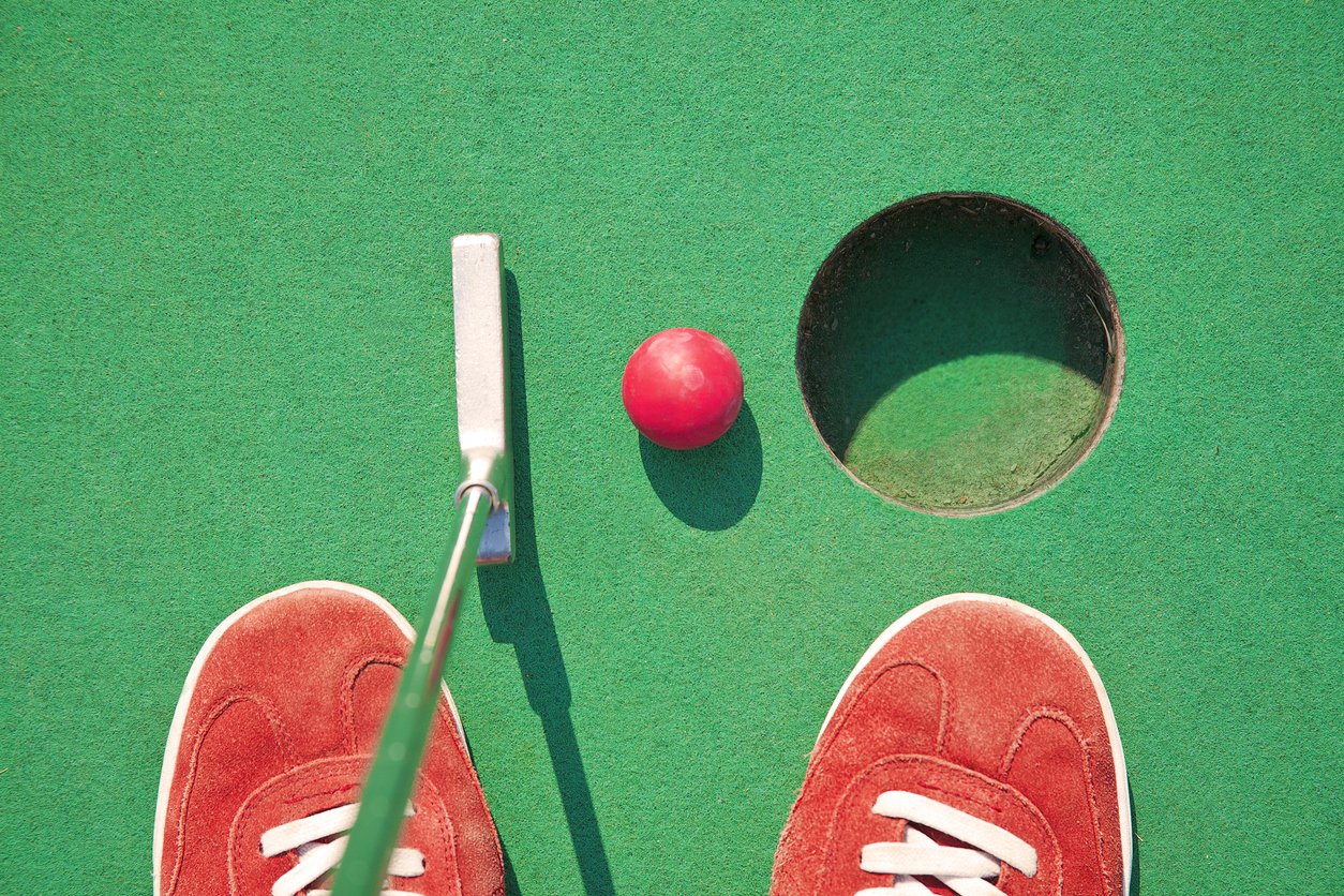 Some putting a golf ball into the hole at a miniature golf course near Jessup